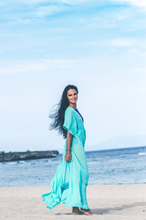 Woman in Teal Dress on Seashore