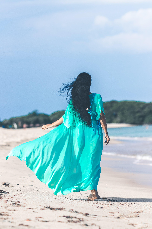 Woman Wearing Teal Dress While Walking Near Body of Water