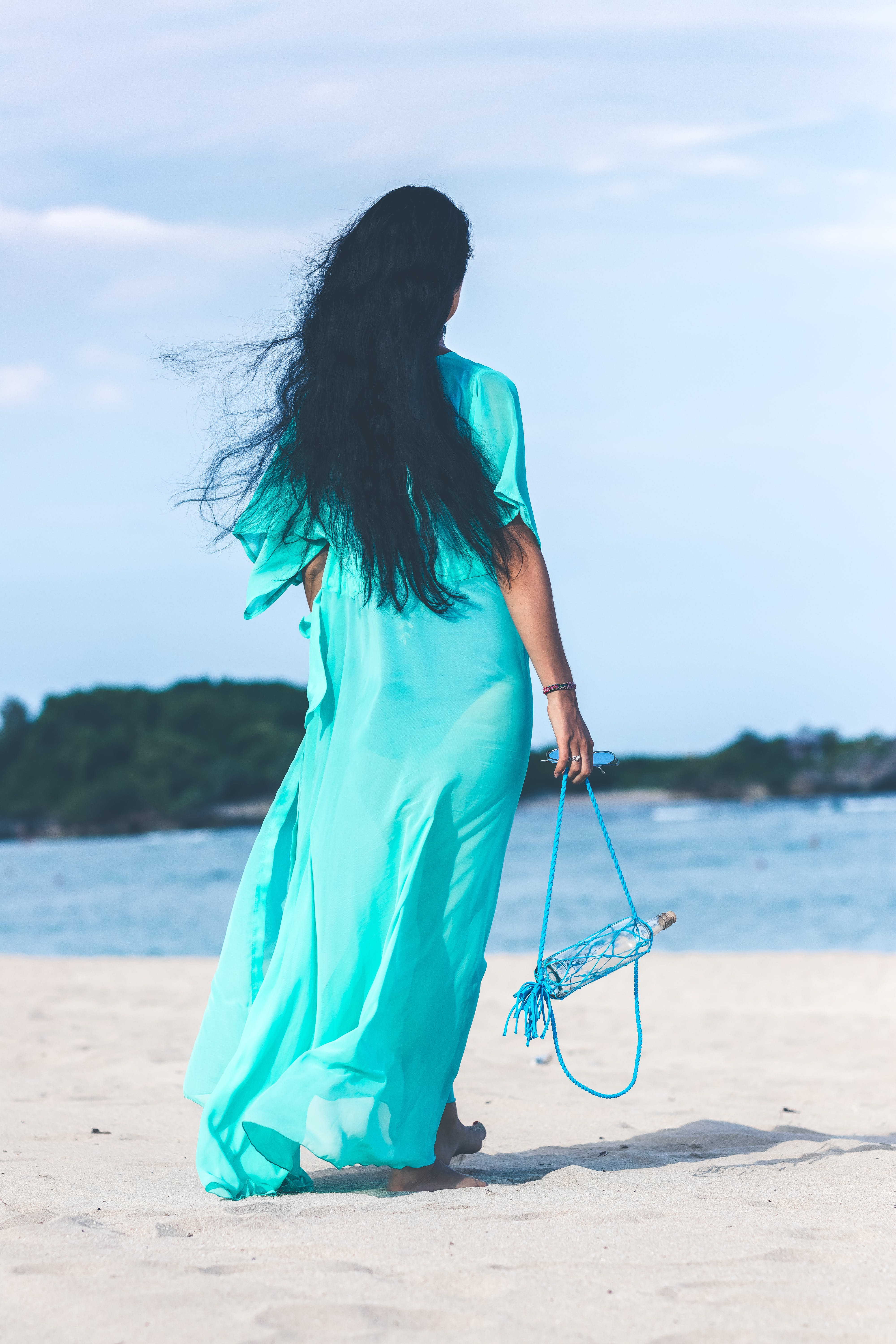 Woman in Teal Dress Standing on Beach
