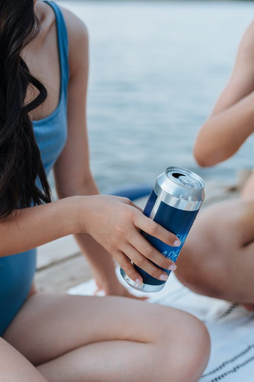 Woman in Swimming Costume Holding Drink Can