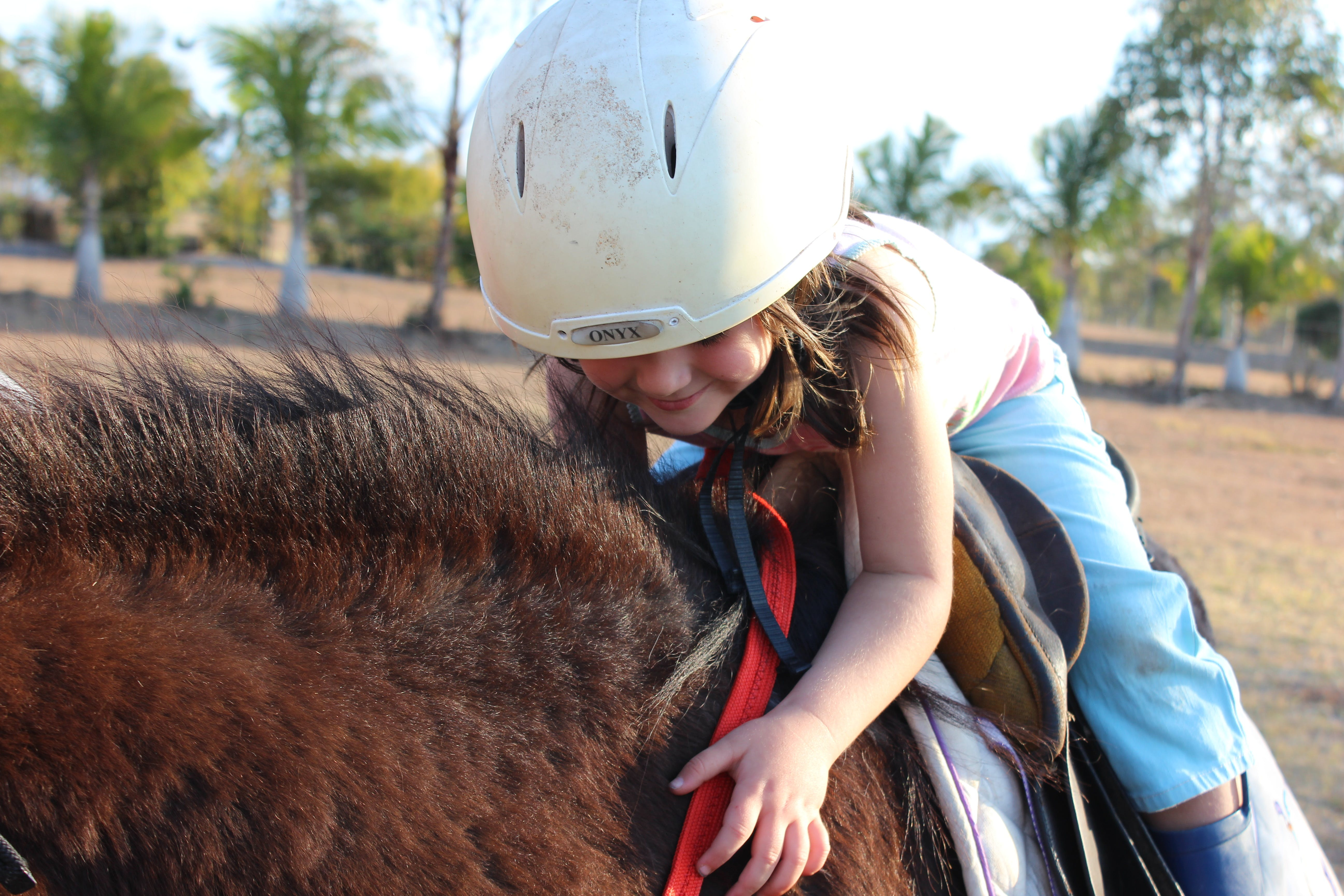 Girl in Blue Pants Riding Brown Animal