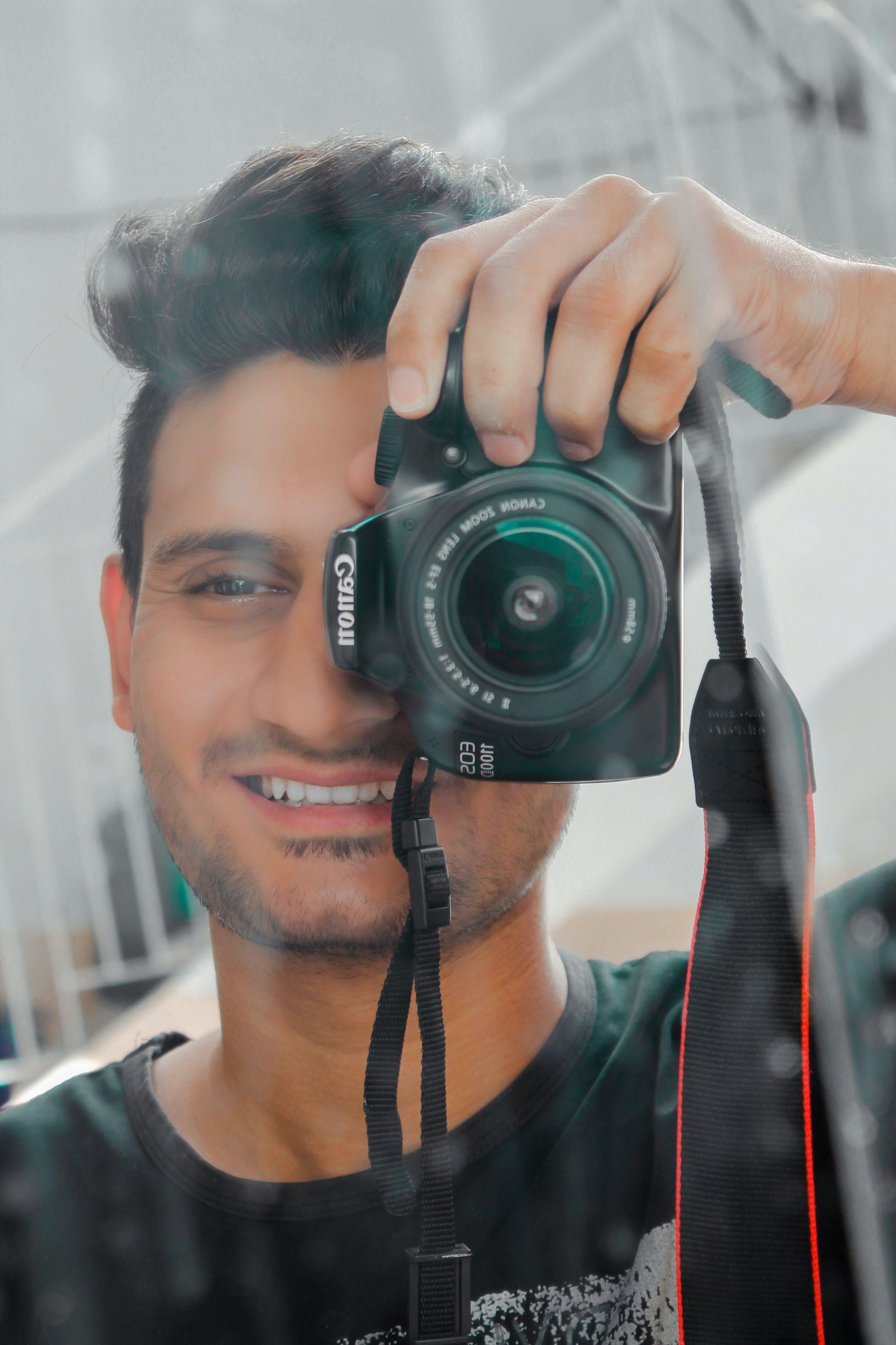 Man Holding Black Canon Eos