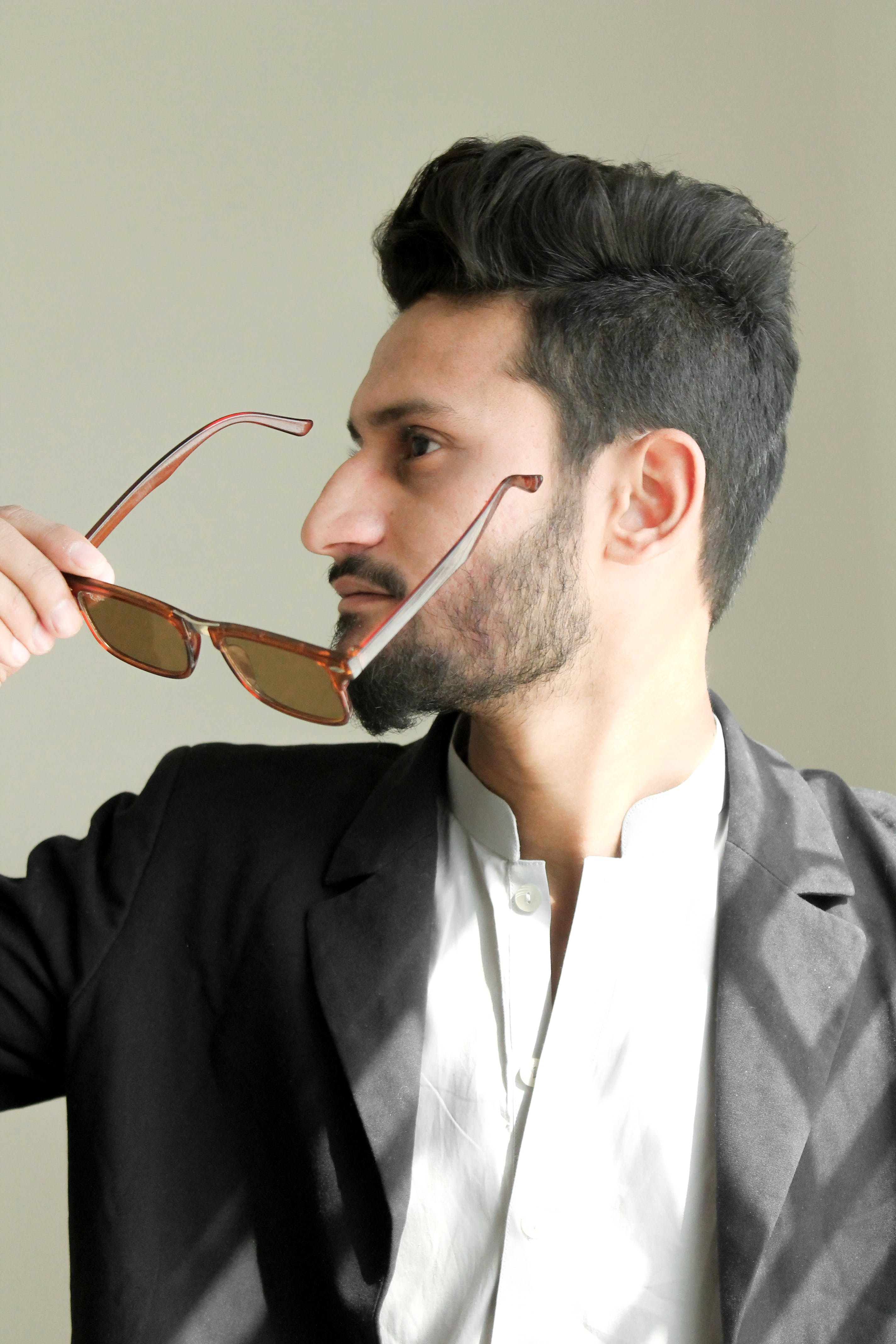 Man Holding Brown Framed Sunglasses With Black Suit