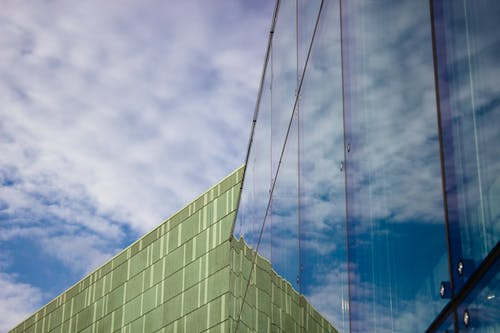 Free stock photo of clouds, glass wall, green building, modern architecture