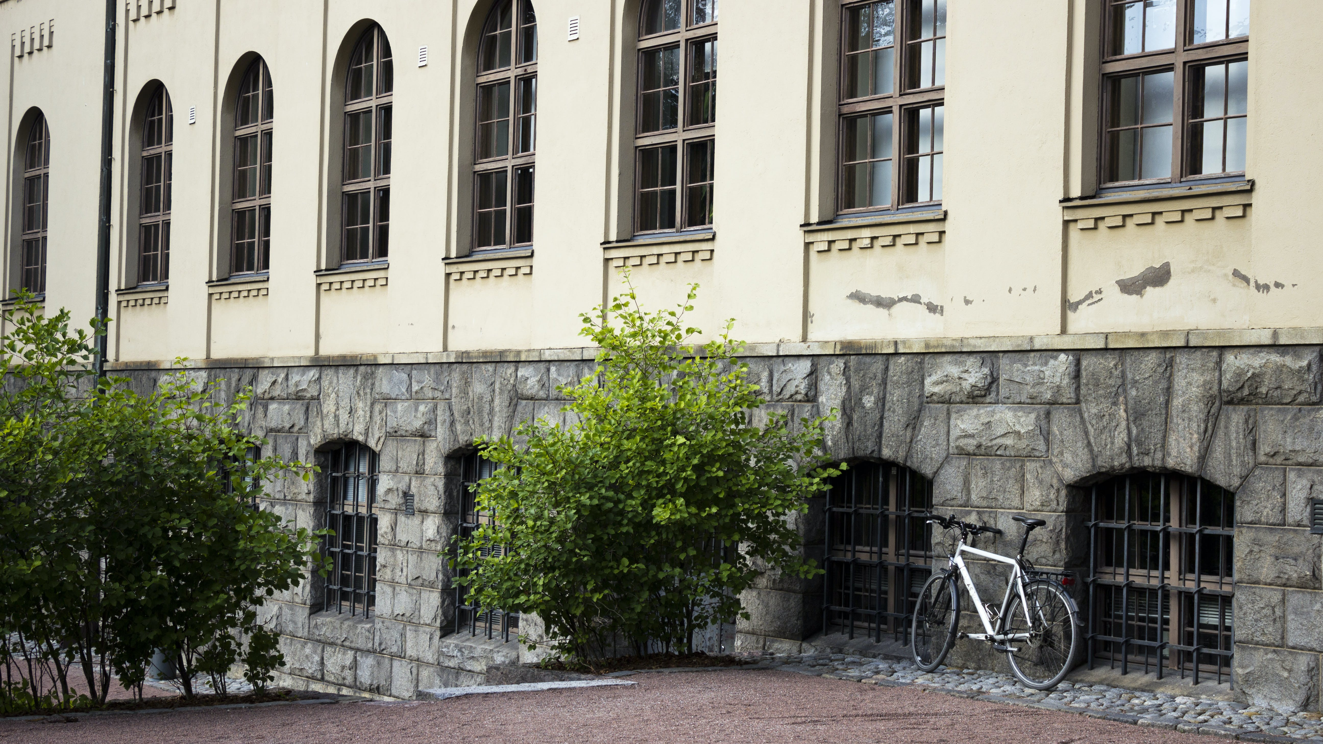 White Bicycle Parked Beside Gray Building