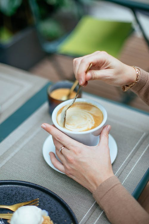 Woman Stirring Coffee in Cup