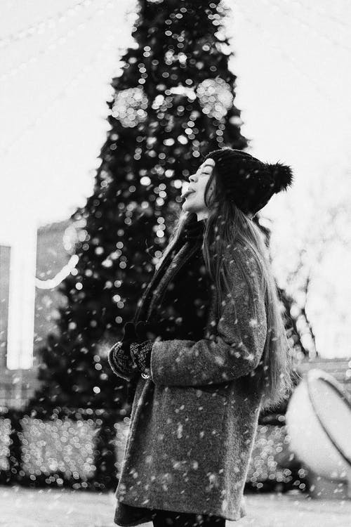 Woman Sticking Out Her Tongue to Catch Snowflakes