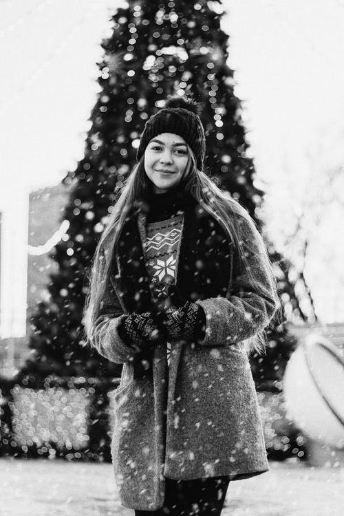 Portrait of Smiling Woman Standing by Outdoor Christmas Tree