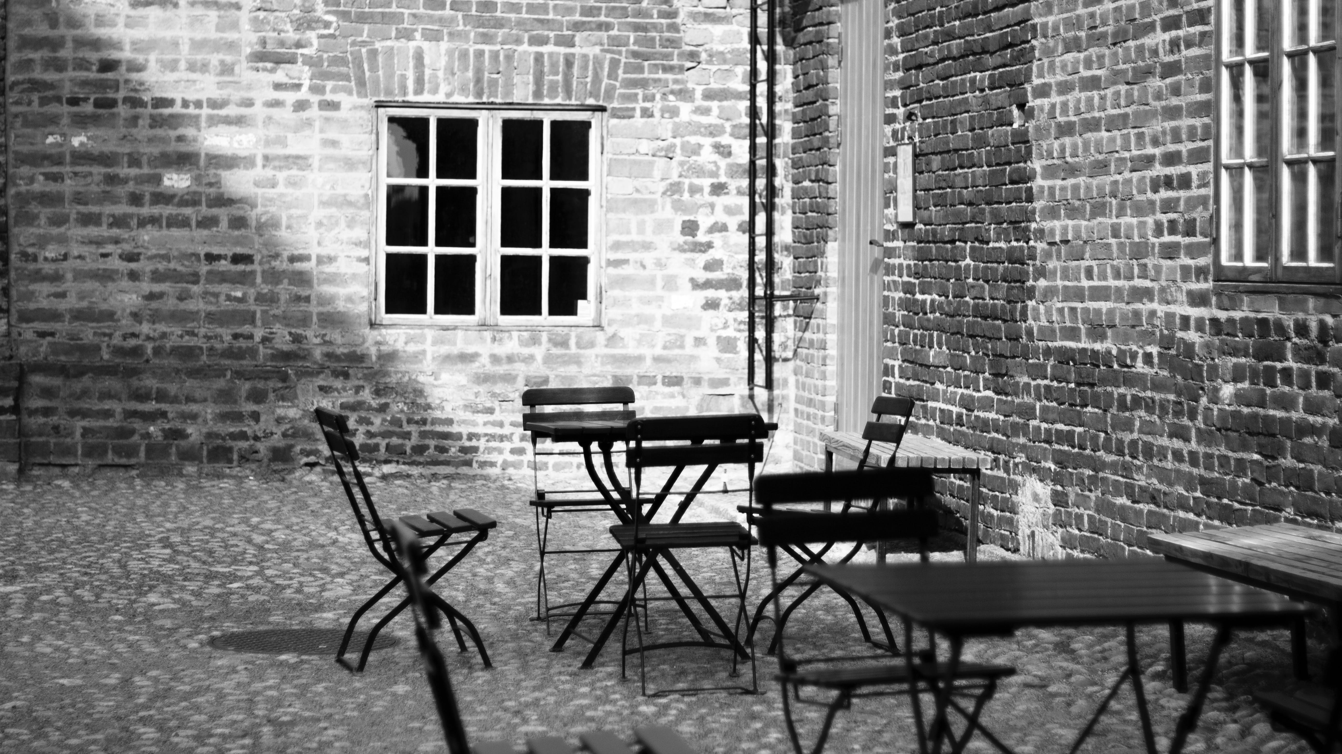 Grayscale Photo of 4-piece Dining Set Near Concrete Building