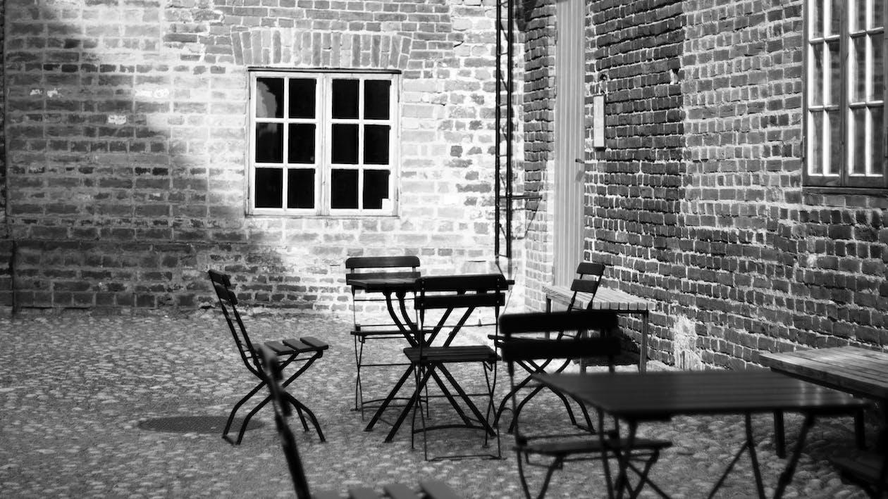 Grayscale Photo of 4-piece Dining Set Near Concrete Building