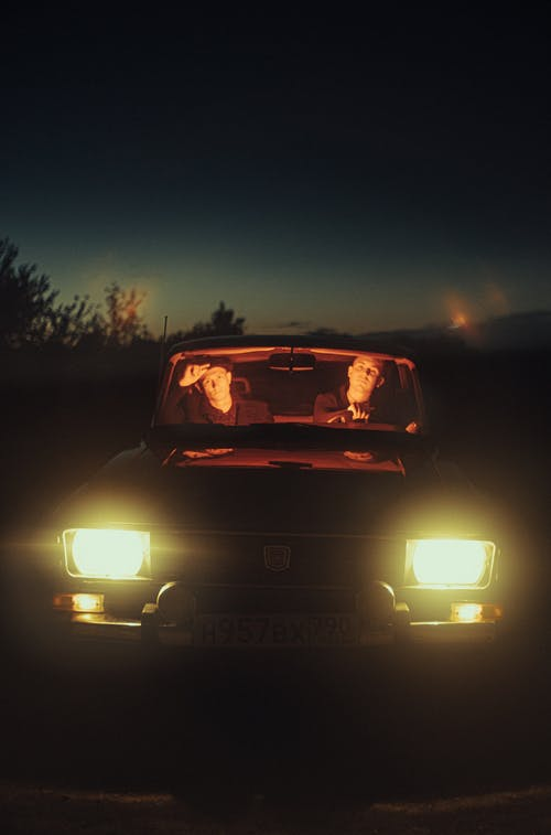 Front View of a Two Males Sitting in Car with Lights Turned On and During Night Time
