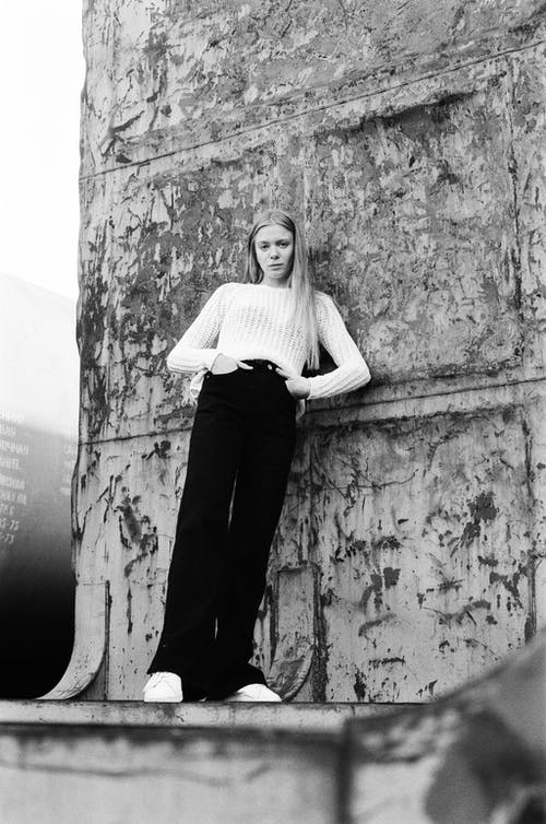 Black and White Photo of Woman Leaning Against Stone Wall