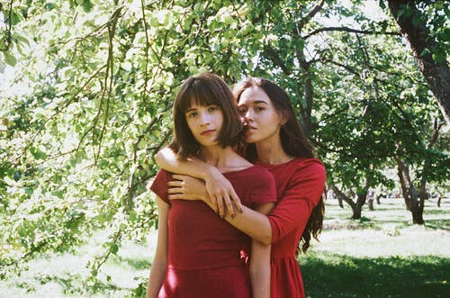 Two Women Hugging in Apple Orchard