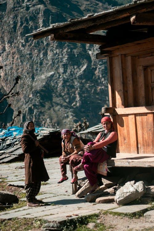 Village Women outside Wooden House