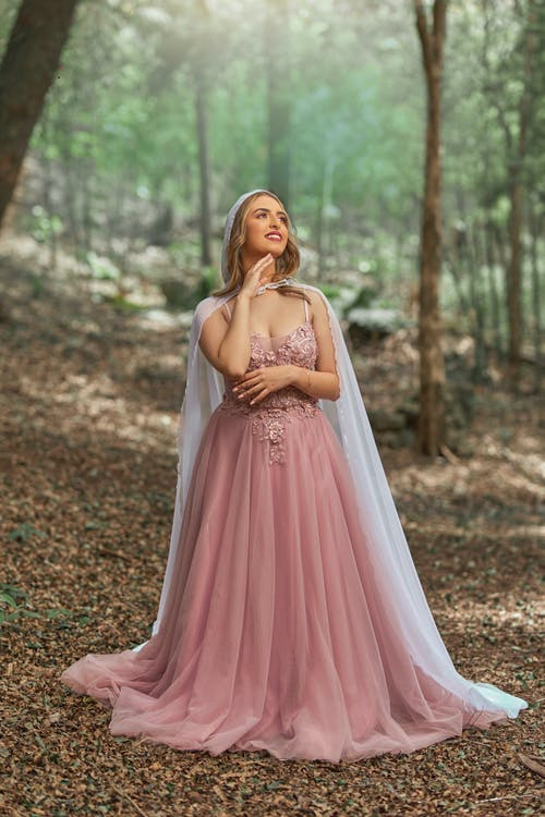 Blond Woman in Princess Gown Standing in Middle of Forest