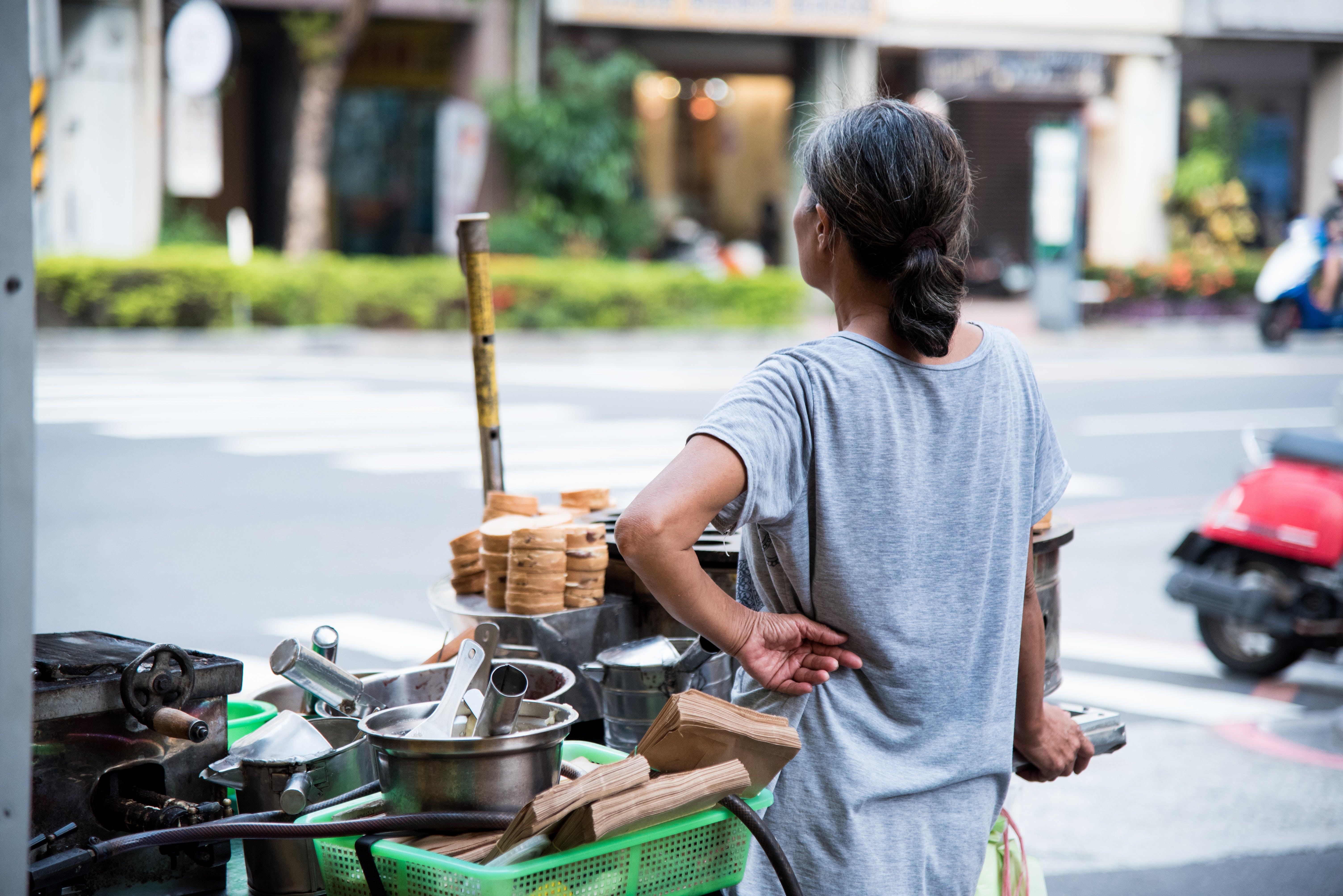 Woman Wearing Gray Shirt Standing Beside Food Cart