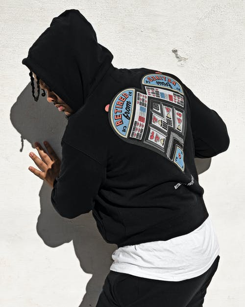 Man with Hood Obscuring His Face Touching White Wall
