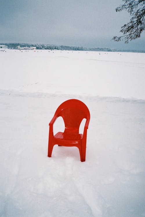 Lone Red Plastic Chair in Snow