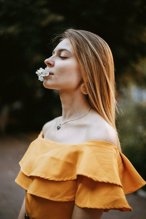 Woman in Mustard Off Shoulder Blouse with Flowers in Mouth