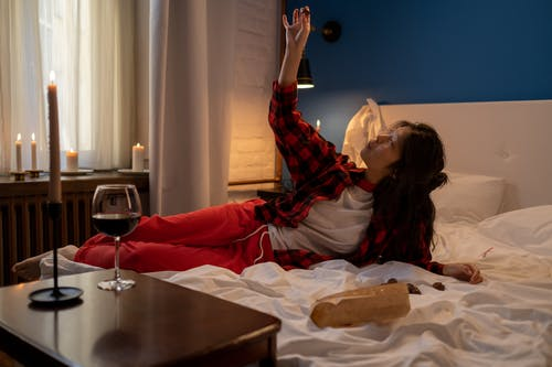 Woman Eating Chocolates in Bed on Valentines Day