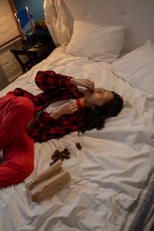 Single Woman lying in Bed and Eating Chocolates on Valentines Day