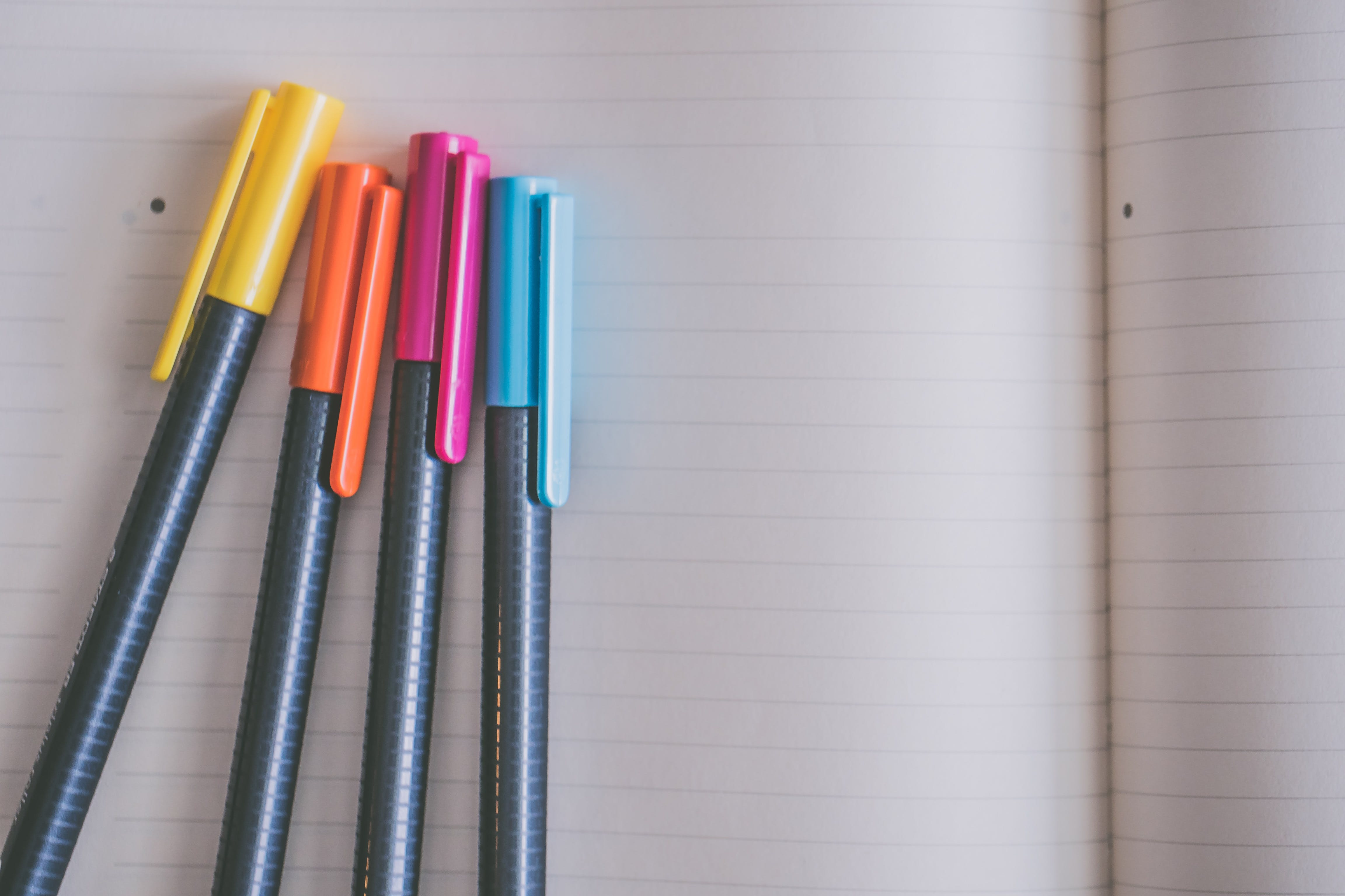 Yellow, Orange, Pink, and Blue Coloring Pens on White Notebook