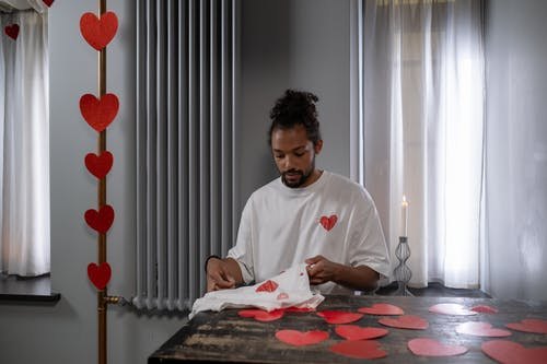 Man Sewing T-shirt with Hearts