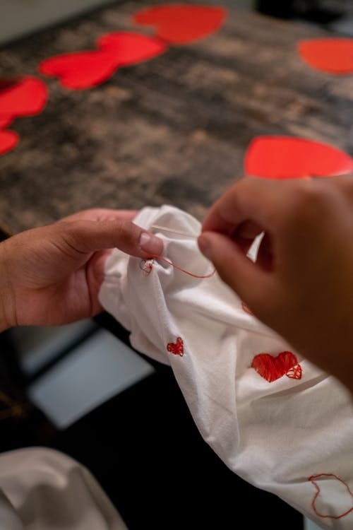 Close up on Mans Hands Sewing T-shirt