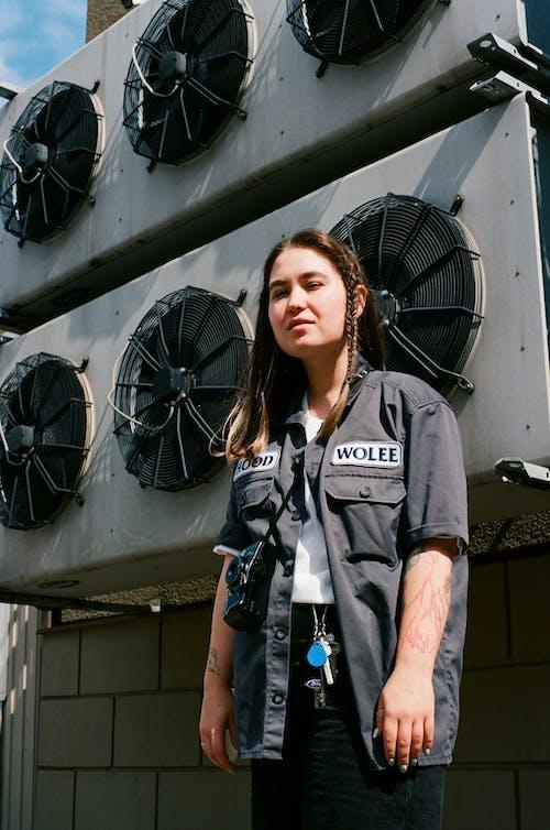 Woman in Gray Crew Neck T-shirt Standing Near Black Pedestal Fan
