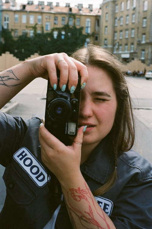 Woman in Black Jacket Holding Black Camera