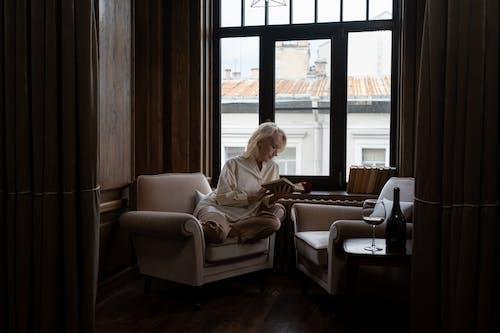 Elderly Woman Reading Book in Room