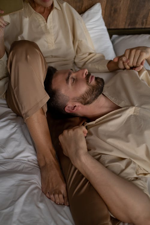 Man Laying on Bed With Woman