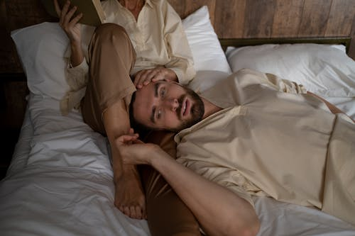 Man Laying on Bed With Woman Who Reading Book