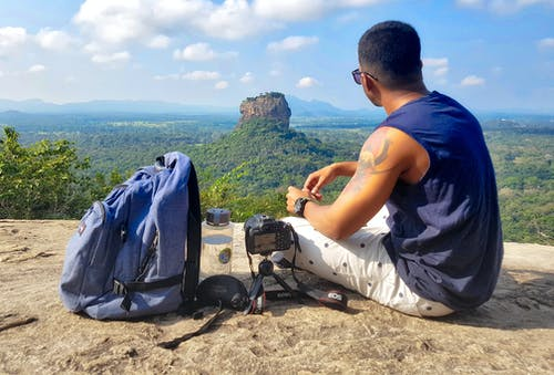 Man Sitting on Top of Gray Cliff Mountain Beside Backpack, Water Bottle, and Camera