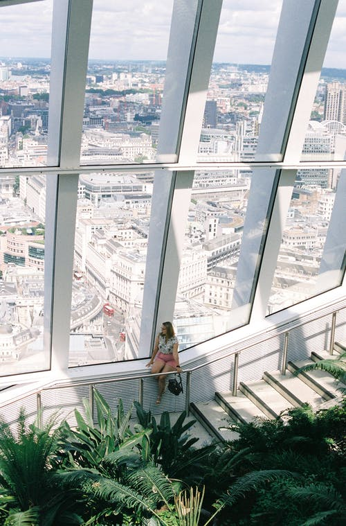 Woman Sitting Next to Large Window, Looking at Cityscape