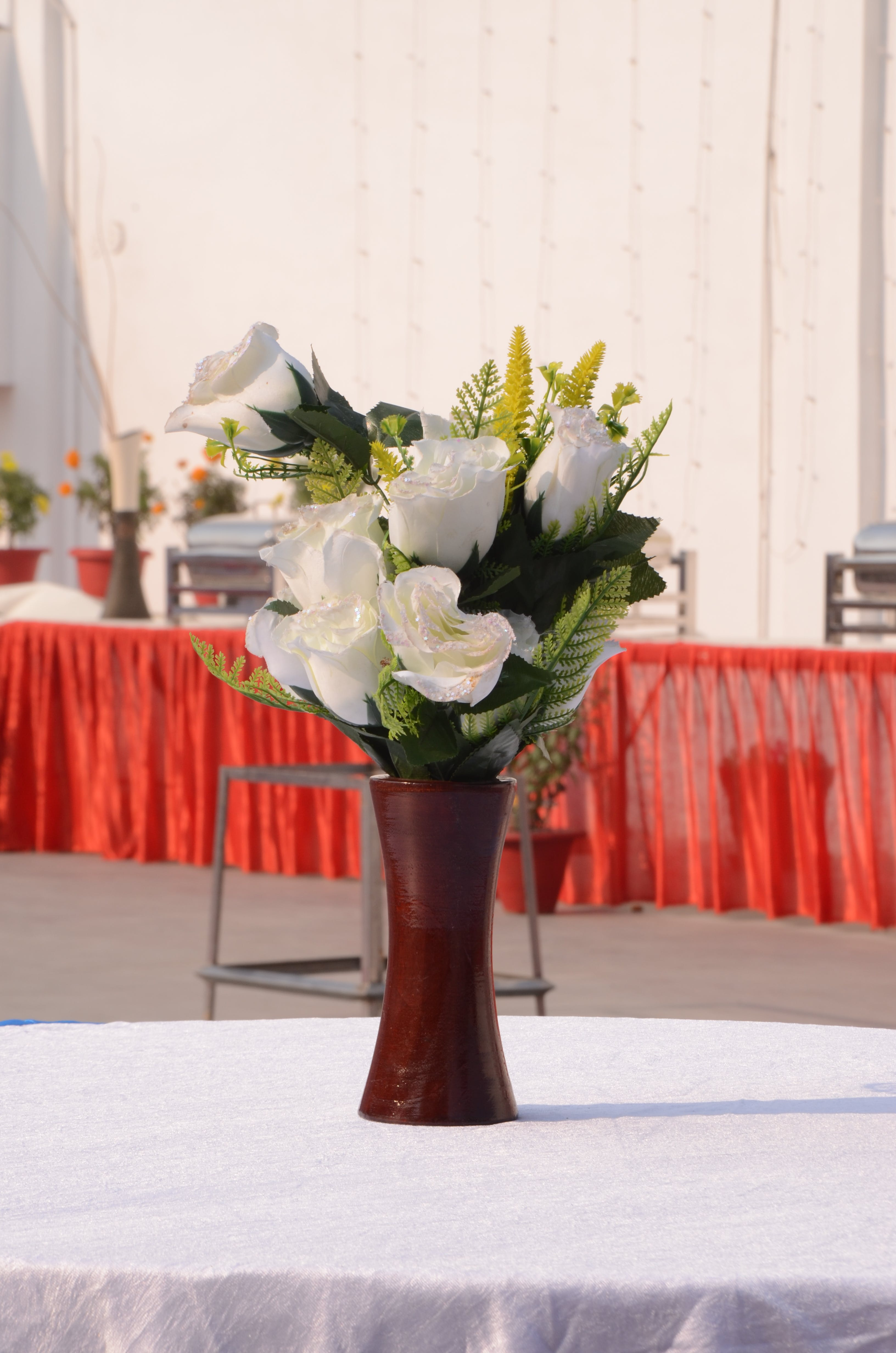White Roses in Red Vase Centerpiece on White Table