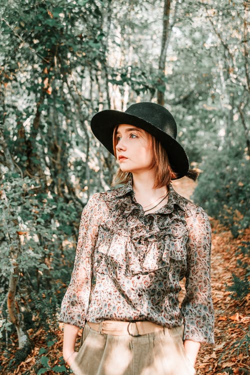 Woman in Black Hat and White and Black Floral Dress Shirt