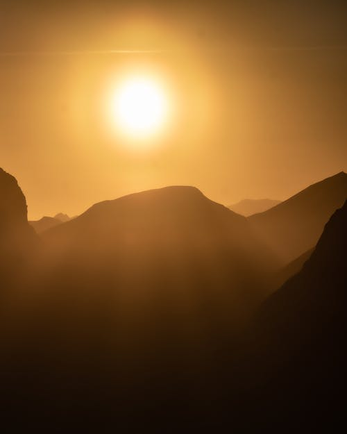 A Silhouette of MountainTop Under The Sun