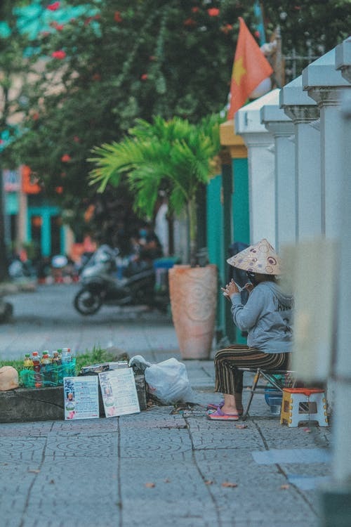 Street Vendor in Conical Hat on Sidewalk
