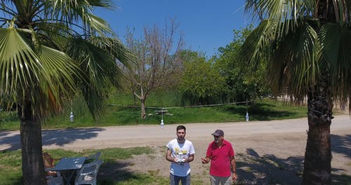 Two Men Flying Drone Around Man-made Island
