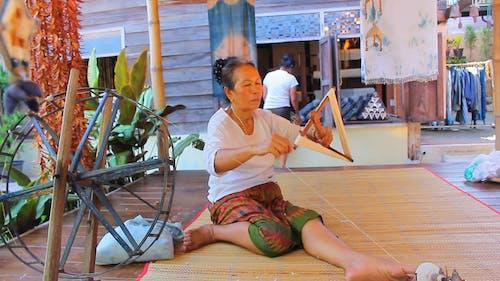 Woman Putting Thread On Triangular Wood