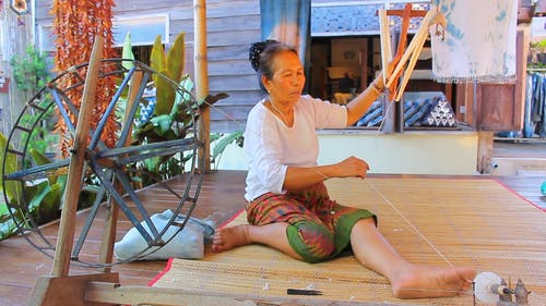 Woman Using Her Foot Pulling Thread