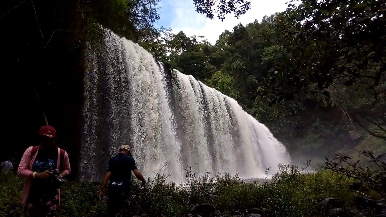 Man Having Photo Taken With Waterfalls As Background