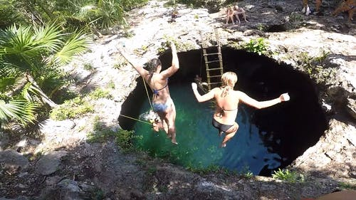 Two Women Jumping Down A Water Hole