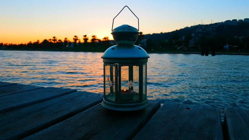 Lantern On A Boardwalk With View Of Sunset