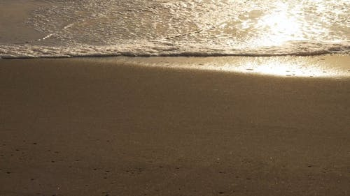 Footprints In The Sand Washed By Wave