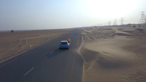 Mini Cooper Traveling Through A Desert