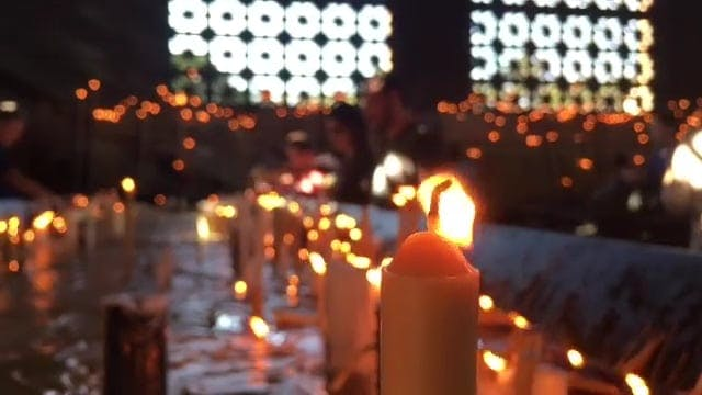 People Lighting Up Candles In The Church