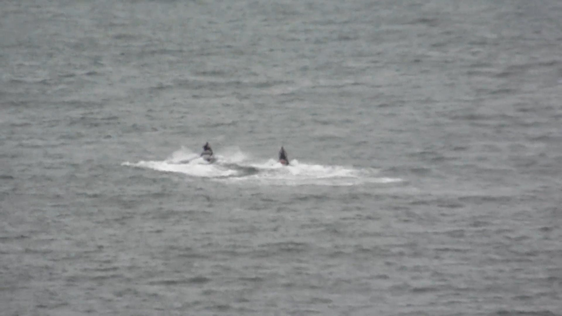People Riding On Jet Skis and A Motorboat