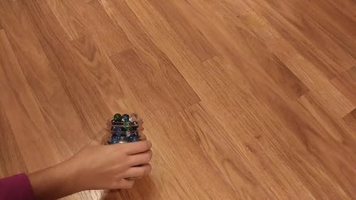 A Bottle Of Marbles Thrown On A Wooden Flooring